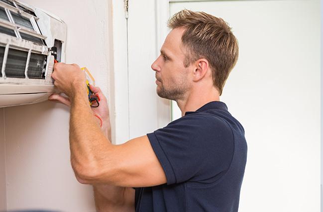 En person står og reparerer et ventilationsanlæg