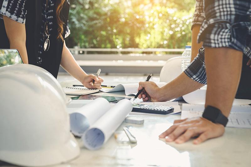 to personer planlægger et byggeprojekt henover et bord med tegninger, en lommeregner og en hjelm