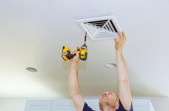 En mand skruer et filter fast i loftet