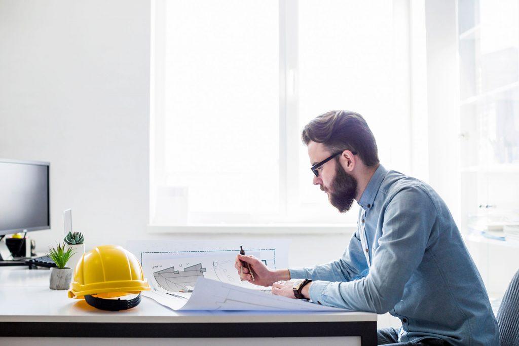 En entreprenør sidder med en tegning